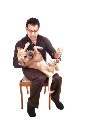 A Hispanic male has his sharpei puppy dog on his lap and playing withhis best friend, sitting on a chair for white background  photo