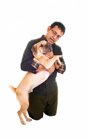 A Hispanic man kneeling on the floor and having his best friend in hisarms, playing with the dog, for white background  photo
