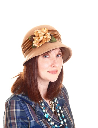 A portrait of a beautiful middle aged woman in a blue shirt and necklacewith a beige hat with flowers on, and red hair for white background  photo
