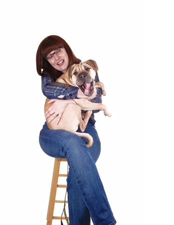 A lovely woman with red hair holding her sharpei dog on her lap, but thedog fight to go down, for white background  photo