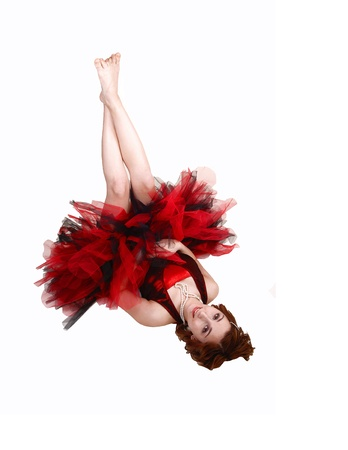 A young pretty teenager in a red and black ballet outfit with a big twillskirt lying on the floor, for white background in the studio  Stock Photo - 13223191