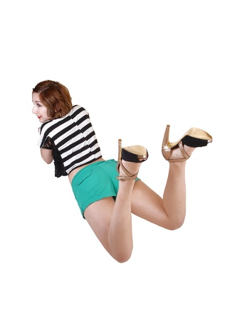 A teenage girl lying on her stomach on the floor in green shorts, a stripedtop and high heels, resting for white background  photo