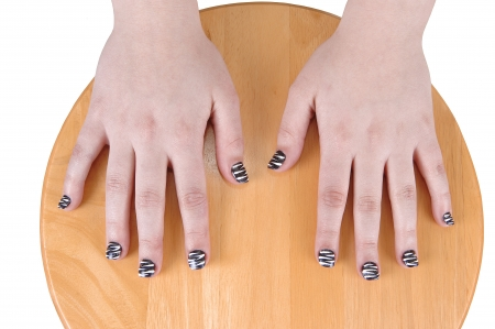 nails: The hands of a young teenage girl with nice polished finger nails, resting on a round wood chair  Stock Photo
