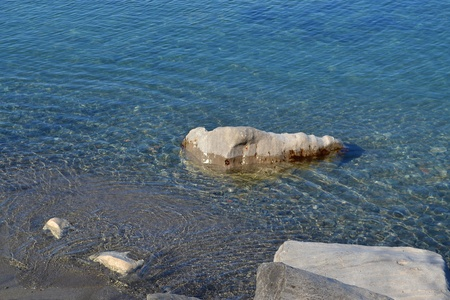 A single big boulder lying in the calm water of lake Ontario in Hamilton onthe shore of lake Ontario