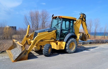 A yellow backhoe sitting on the street in Stoney Creek, Ontario close tothe lake Ontario, on a beautiful sunny day in early spring