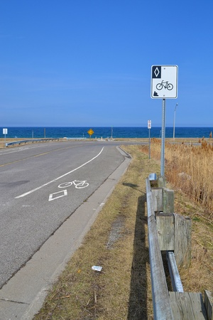 lain: On a rural road in Stoney Creek, Ontario, a sign and markings on the streetshows this is a designated lain for bicycles, background lake Ontario  Stock Photo