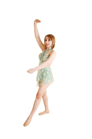A beautiful teen ballet girl practicing in the studio for white backgroundin her light green short dress