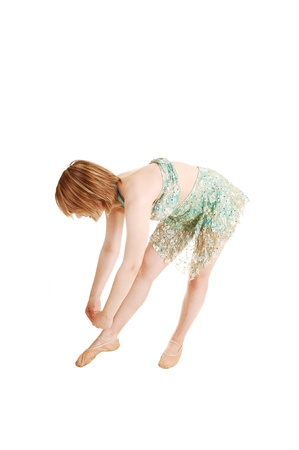 A dancing young ballet teenager in a light green dress and with blondhair in the studio for white background