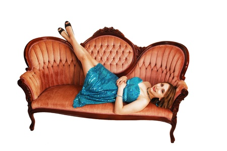 An young pretty teenager girl in a turquoise dress lying on a old fashionpink sofa, her legs up on the back of the couch, for white background  photo