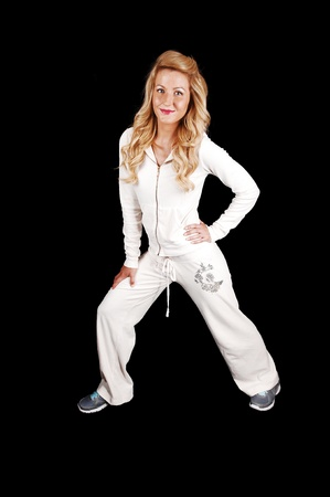 sportingly: A pretty slim and blond woman standing in her white tracksuit inthe studio, smiling, for black background