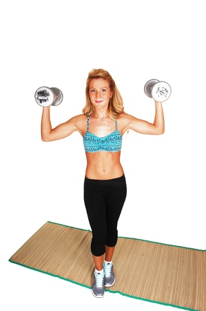 A slim young woman exercising with weights on a mat, in an sportsbra and black pants, for white background  Stock Photo - 13556109