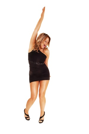 A pretty woman in a black short dress heaving fun, dancing and liftingone arm up and her mouth open for white background  photo