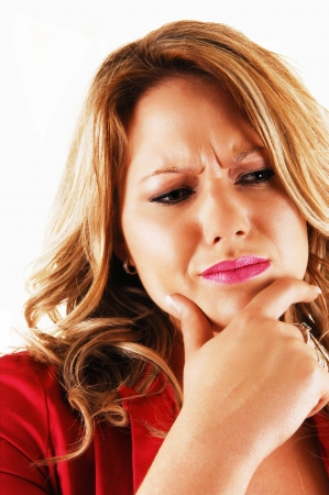 A young blond woman holding her chin with one hand and lookingvery serious about a problem in closeup over white  photo
