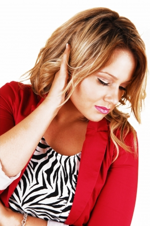 A beautiful young woman in a nice pose looking down with one handon her head, in a red jacket for white background  photo