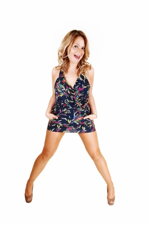 A young pretty and happy woman standing with her legs spread, laughingwith her mouth open in a short dress for white background