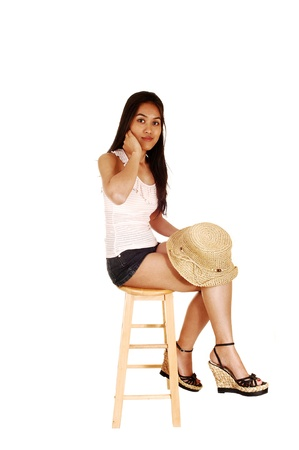 seated: A slim and young Asian woman sitting on a chair in shorts and whitetop, holding a straw hat in her hand, for white background  Stock Photo
