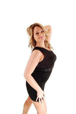 A young blond woman in a black dress standing in the studio forwhite background and showing her nice figure  Stock Photo - 13899662