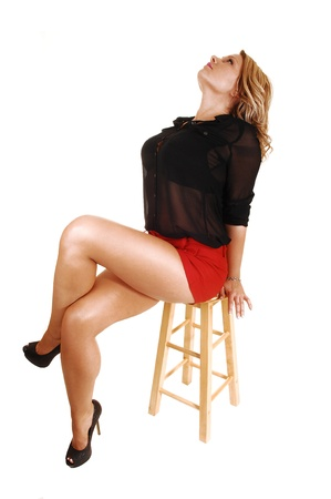 A young blond woman sitting on a chair in red shorts and a black blouselooking up and showing her nice long crossed legs, over white photo