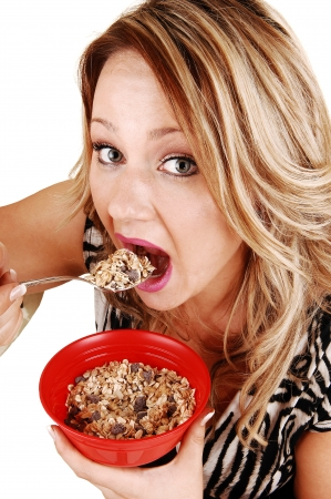 A very hungry young woman eating her breakfast from a red bowl,standing for white background, no time to sit down  photo