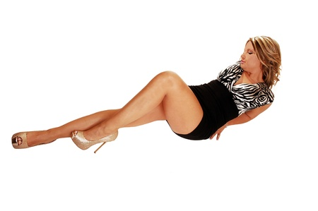 A beautiful young woman in a black dress lying on the floor, showingher nice long legs with heels, for white background  photo