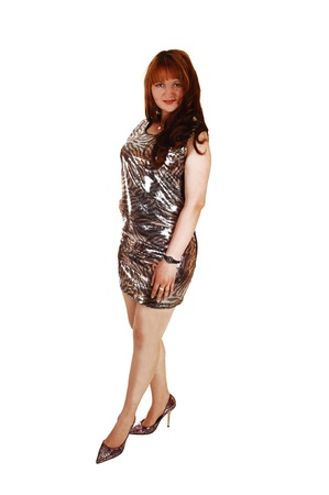 A lovely young woman with long red hair standing for white backgroundin a silver color evening dress and high heels  photo