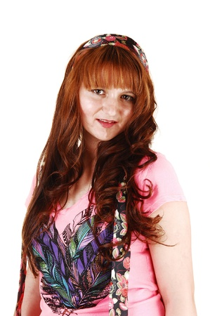 A young woman with long red hair and a pink top standing for aportrait shot for white background  photo