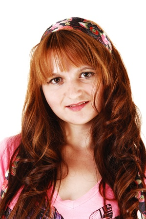 A closeup of a pretty young woman with long red hair for white backgroundwith a headband in her hair, looking into the camera  photo