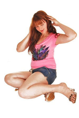 A young pretty woman with long red hair sitting for white background onthe floor in jeans shorts and a pink top and high heels  photo
