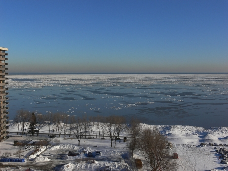 Ice on the lake Ontario in winter under nice blue sky and snow on the parking loot from the apartment building  photo