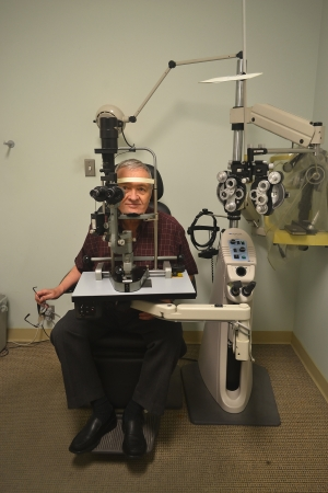 A older man sitting in the office of an optometrist checking out hiseyesight