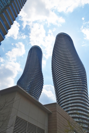 In the city of Mississauga Ontario, Canada two ultramodern round andtwisted high rise building around other high rises  photo