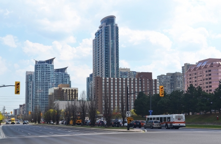 The skyline of Mississauga Ontario, Canada, with high rise buildingsunder partly cloudy sky, with a intersection in front of