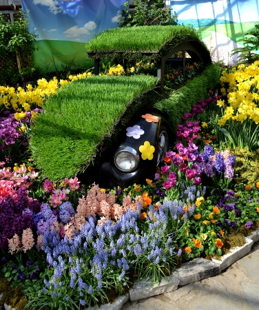 An old VW decorated with grass and flowers in a indoor flower showin the spring, with beautiful flowers on all colors around