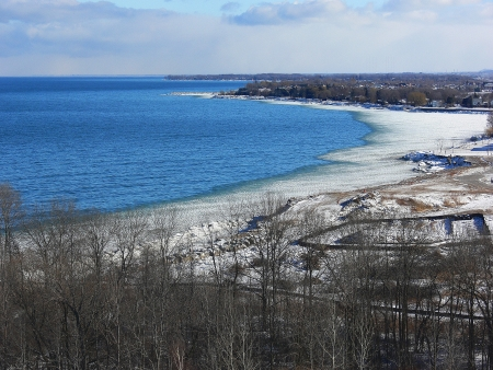 The shore ling of lake Ontario in winter with ice on the shore line andbeautiful blue water  photo