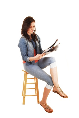 A young pretty woman sitting on a chair in blue thighs and a bluejeans jacket and reading the newspaper for white background