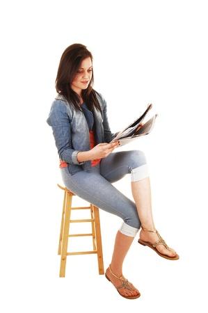 mujeres sentadas: Una hermosa mujer joven sentada en una silla en los muslos azules y una chaqueta de bluejeans y leer el periódico para el fondo blanco