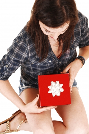 A young woman seen from the top, in shorts and a shirt with a redwrapped gift in her hand, for white background  photo