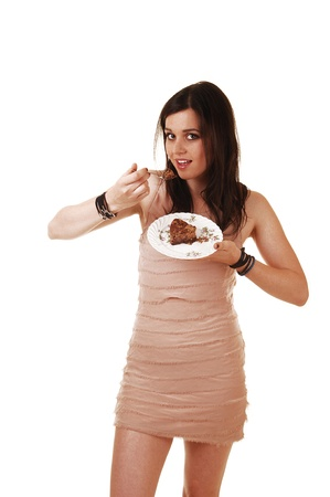 A young slim woman in a beige dress and with long brunette hair standingin the studio and eating a piece of chocolate cake, for white background  photo