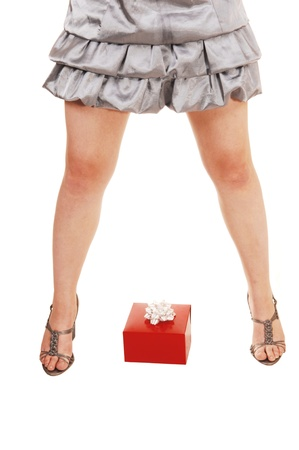 spread legs: A closeup of a young girls spread legs with high heels and a red presentlying on the floor between her legs, for white background  Stock Photo