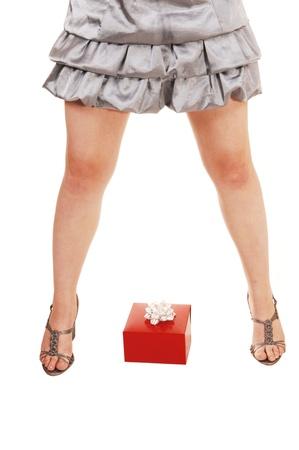 beine spreizen: Eine Nahaufnahme einer jungen M�dchen gespreizten Beinen mit hohen Abs�tzen und einem roten presentlying auf dem Boden zwischen ihren Beinen, f�r wei�en Hintergrund