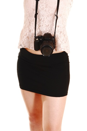 Closeup of the midsection of a young woman with a camera around herneck, in a short black skirt and beige blouse for white background  photo