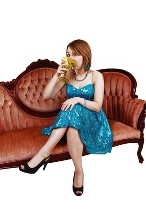 An young girl sitting on a pink antique couch in a turquoise evening dressdrinking a soft drink in heels for white background  photo