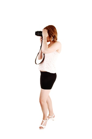 A young teenager girl in a black miniskirt and high heels standing in thestudio taking pictures with a DSLR, for white background  photo