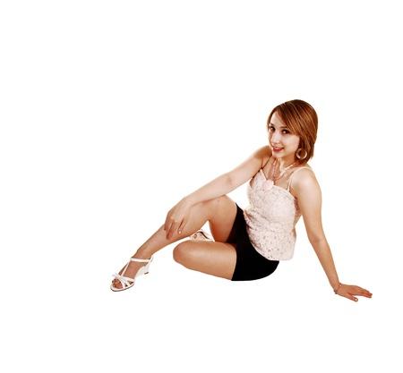 minijupe: Une adolescente jolie jeune dans une mini jupe noir et beige pour blousesitting fond blanc sur le sol et se d�tendre