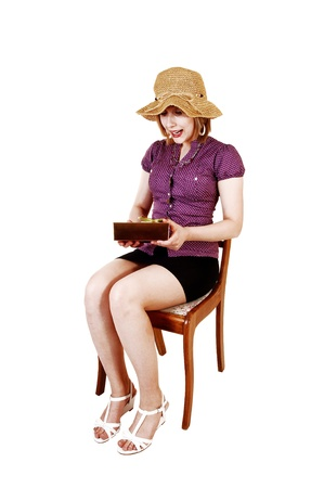 A young pretty girl sitting on a chair in a black skirt and beige blouseand a straw hat, just got a present, for white background  photo