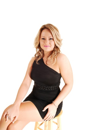A beautiful blond woman sitting in the studio for white background ina black short dress and smiling into the camera  Stock Photo