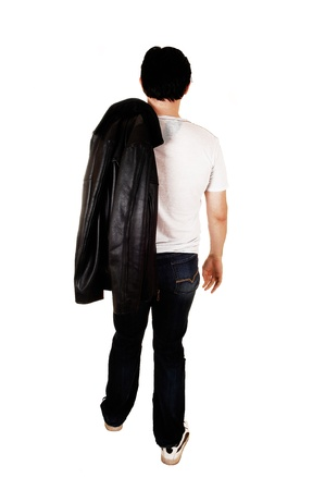 A young handsome man with a black leather jacket walking from theback in the studio for white background  photo
