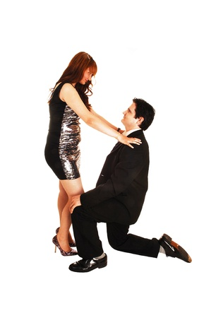 A young man, kneeling on the floor and proposing to his fiancée, bothin evening dressing, for white background