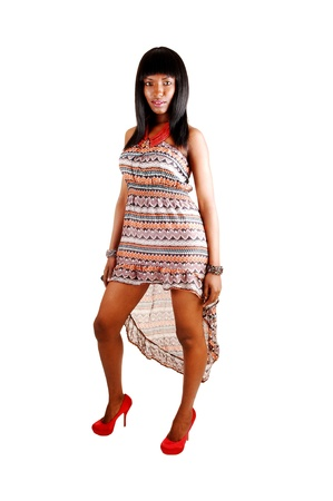 A pretty African America in a dress and red heels standing for whitebackground with her long black hair  Stock Photo