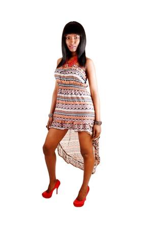 tacones rojos: Una hermosa Latina de �frica en un vestido y tacones rojos de pie por whitebackground con su pelo largo y negro